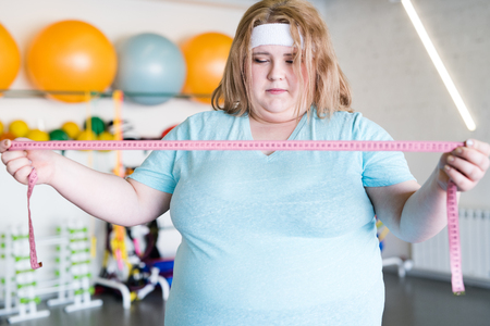 Anxious Obese Woman with Tape Measure Stock Photo