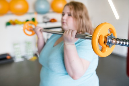 Obese Woman Working Out with Barbell