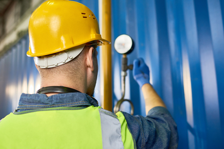 Back view portrait of worker wearing hardhat checking pressure systems while working at modern plant, copy space Stock Photo