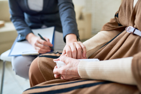 Close up of female psychologist holding hand of senior woman during therapy session, copy space Banque d'images