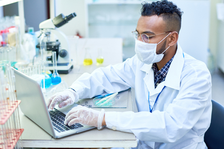 Busy scientific researcher using laptop to enter data