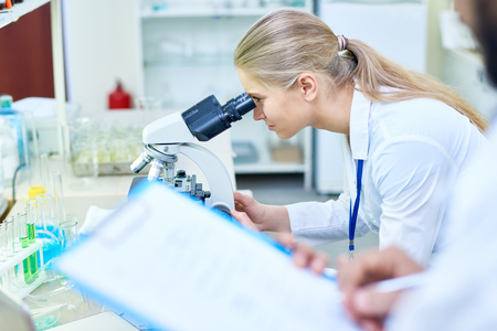 Serious medical student analyzing sample through microscope