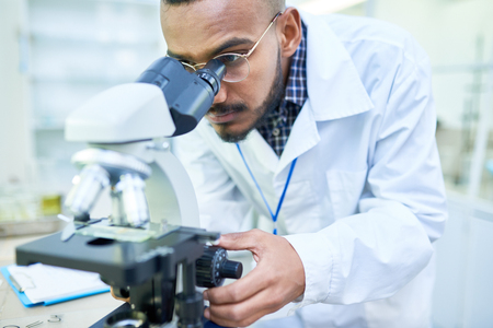 Modern handsome biologist adjusting microscope to zoom image