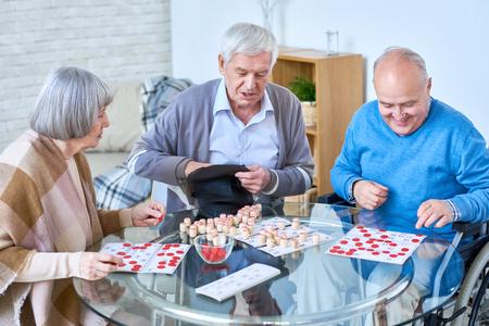 Amigos mayores jugando lotería en la casa de retiro