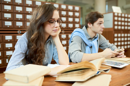 Pensive college students in academic library