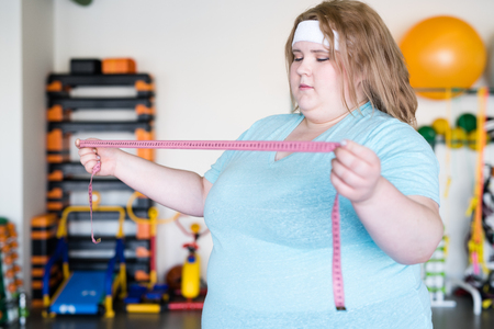 Obese Woman Holding Tape Measure Stock Photo