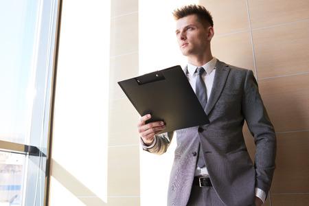 Handsome Businessman Holding Clipboard Imagens