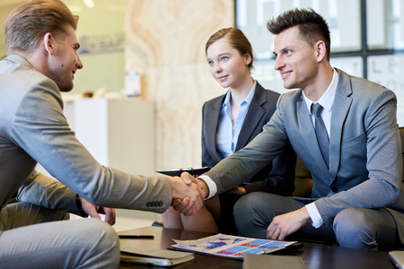 Business People Shaking Hands at Meeting Table