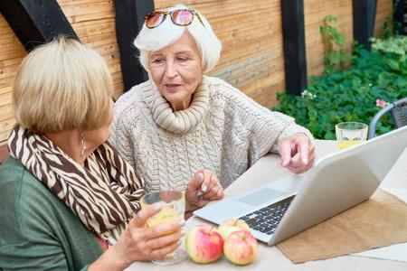 Two Senior Women Using Laptop Outdoors