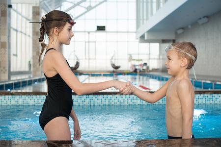 Zelfverzekerde junior zwemmer die elkaar begroeten in het zwembad