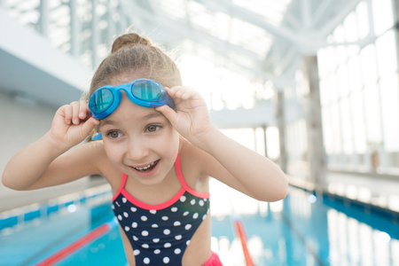 Excited pretty swimmer in indoor pool Stock Photo