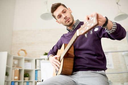 Adjusting Guitar at Modern Office 写真素材