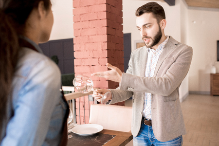 Strict restaurateur examining clearness of wineglass