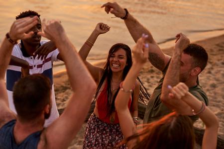 Interracial friends dancing in ecstasy outdoors