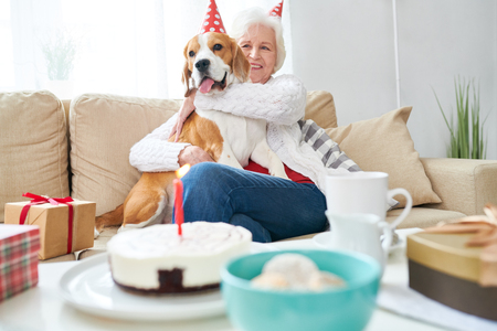 Excited senior owner celebrating dogs party