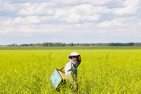 Young Apiarist Standing in Meadow Stock Photo - 100055071