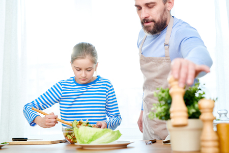 Dad and Little Daughter Preparing Salad