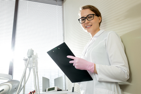 Cosmetologist Holding Clipboard Posing in Office