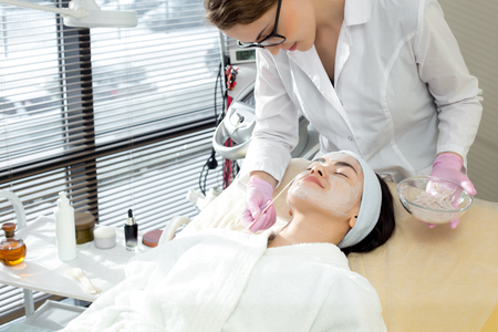 Female Cosmetologist Applying Face Mask Reklamní fotografie - 100439617