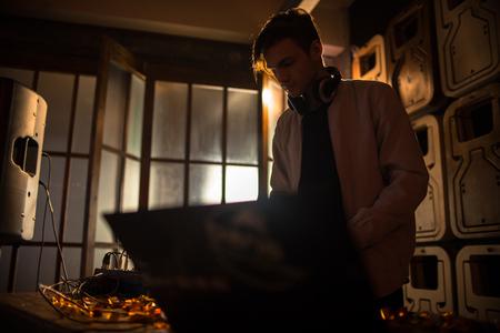 Young DJ Playing in Dark Club Stock Photo