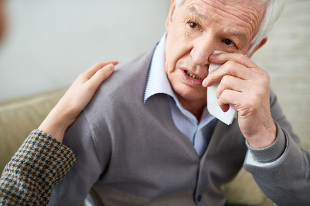 Crying elderly man having nurse help