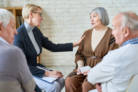Woman consoling senior patients on meeting