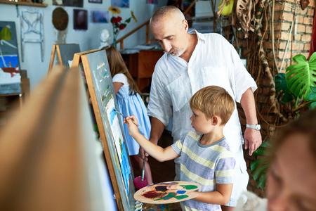 Art  Teacher Helping Little Boy Banque d'images