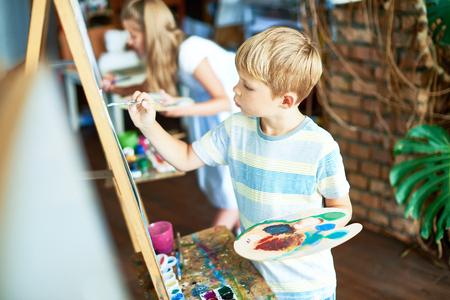 Schattige jongen schilderij in kunstklasse