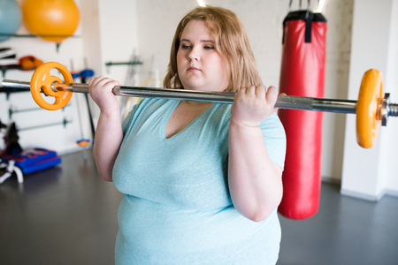 Obese Woman Holding Barbell Standard-Bild