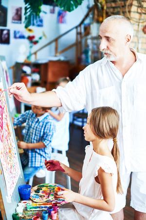 Senior Art Teacher Helping Girl Banque d'images