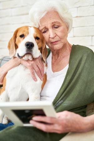 Traurige ältere Frau, die Hund umarmt