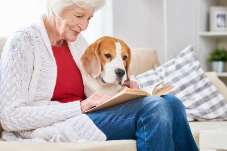 Loving Senior Woman Reading with Dog