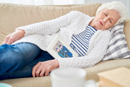 Senior Woman Falling Asleep with Photo of Husband
