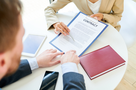 High angle closeup of elegant businesswoman holding contract documentation showing it to client or partner and explaining terms of deal sitting at round table during meeting in office. Reklamní fotografie
