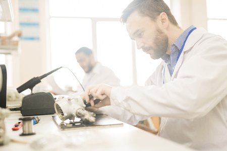 Experienced technician repairing pressure gauge