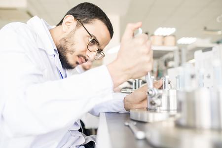 Arabian technician replacing bearing in factory shop