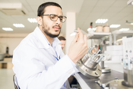 Concentrated Arabian engineer viewing detail of technical equipm