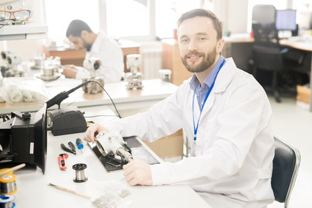 Qualified lab technician analyzing manometer in workshop