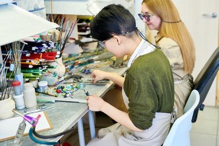 Two Female Artists Working in Glassworking Studio