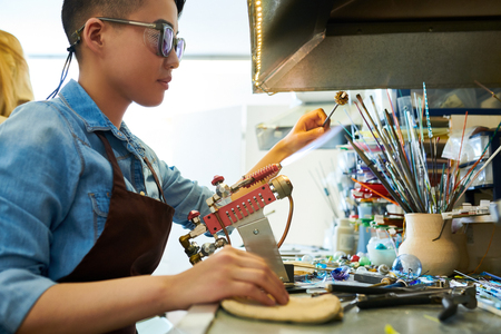 Asian Artist Shaping Glass in Flame Stock Photo