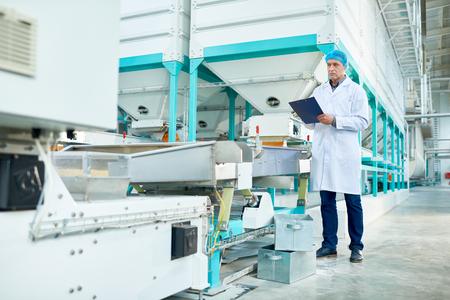 Älterer Mann, der in der modernen Fabrik arbeitet
