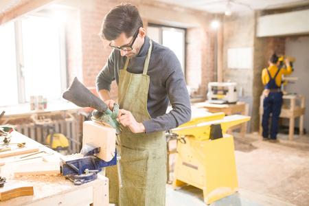 Modern Carpenter in Sunlit Workshop Stock Photo