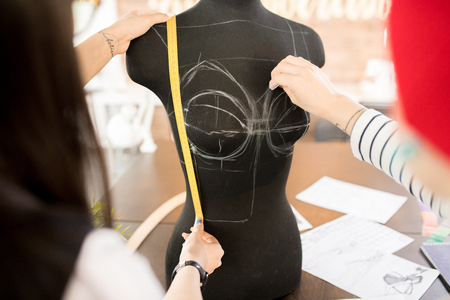 Back view  portrait of two women working in fashion design and collaborating on project , focus on sewing dummy traced for pattern making Фото со стока
