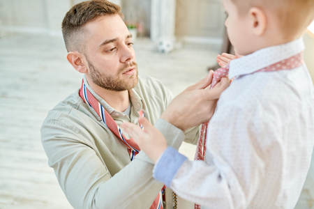 Loving Dad Knotting Tie with Little Son 스톡 콘텐츠