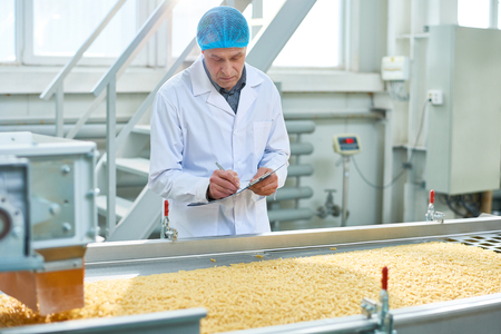 Senior Worker Overseeing Production of Food Stock Photo