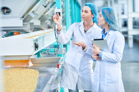 Two Young Women Working at Modern Food Factory