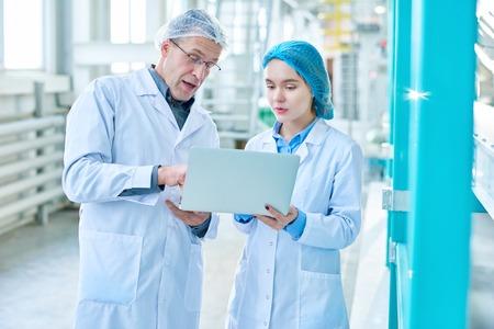 Deux travailleurs utilisant un ordinateur portable dans une usine moderne