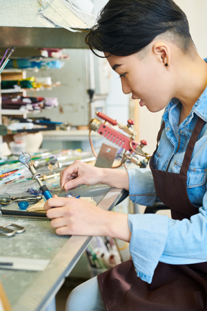 Asian Artist in Lampworking in Studio Stock Photo