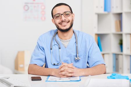 Fröhlicher nahöstlicher Doktor, der am Schreibtisch posiert