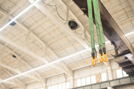 Ropes with hoists hanging from construction ceiling